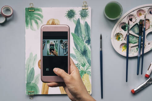 Cropped image of hand photographing watercolor painting with smartphone at table - MOMF00730