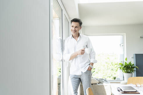 Mature man leaning on window, drinking coffee at home - UUF18083