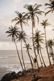 Full length of woman enjoying by palm trees while looking at sea against sky in Sri Lanka - LHPF00721