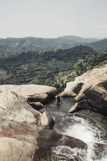 High angle view of young woman swimming in stream amidst rock formation at Sri Lanka - LHPF00730