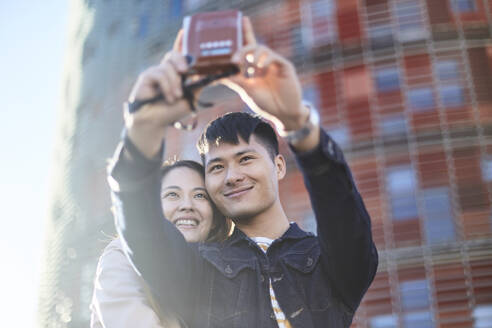 Portrait of couple talking selfie with instant camera, Barcelona, Spain - DVGF00012