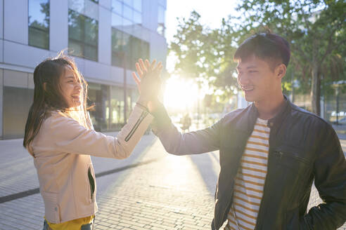 Smiling couple high fiving at sunset - DVGF00021
