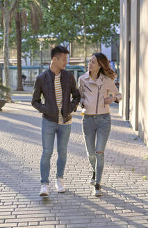 Couple wearing jeans and leather jackets walking on street in the evening - DVGF00033