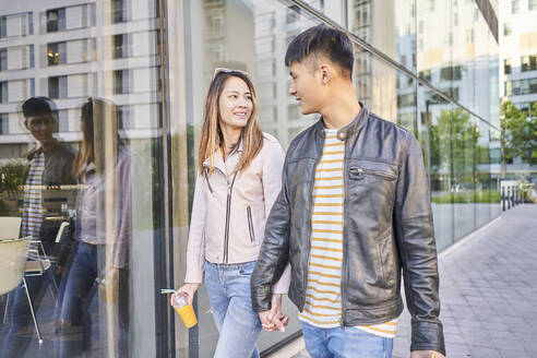 Couple wearing leather jackets walking hand in hand in the city - DVGF00051