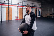 Young man training, lifting atlas ball in gym - CUF52032