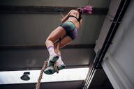 Young woman training, climbing up exercise rope in gym, low angle view - CUF52053