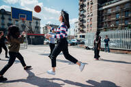 Young female and male adult friends playing basketball on city basketball court - CUF52074