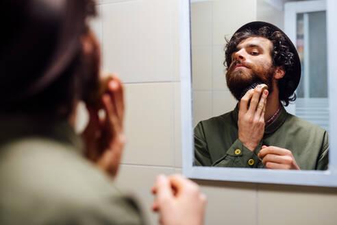 Bearded young man brushing beard in bathroom - CUF52155