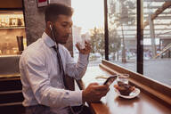 Businessman using smartphone at tea time in cafe - CUF52170