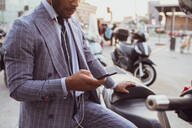 Businessman using smartphone by motorcycle - CUF52173
