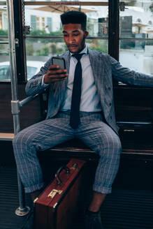 Businessman using smartphone on tram in city - CUF52185