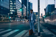 Businessman using smartphone by pedestrian crossing, Milano, Lombardia, Italy - CUF52188