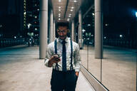 Businessman using smartphone, walking past mirrored wall of office building, Milano, Lombardia, Italy - CUF52197