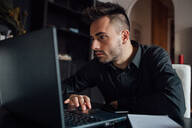 Man using laptop in home office - CUF52257