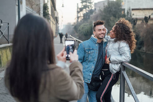 Friends taking photograph by river, Milano, Lombardia, Italy - CUF52287