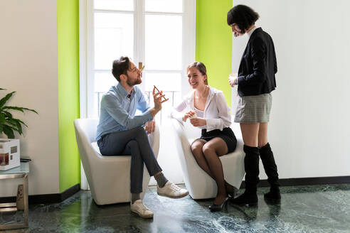 Male and female business creatives looking at smartphone in office - CUF52344