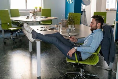 Young male business creative with feet up looking at smartphone in office - CUF52347