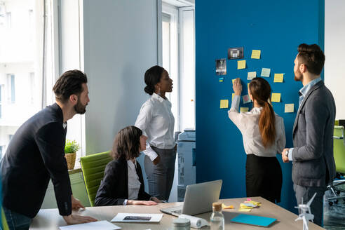 Young male and female business creative team brainstorming with sticky notes in office - CUF52356