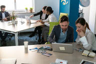 Young male and female business creative teams sharing meetings in open plan office - CUF52359