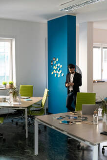 Young male business creative looking at smartphone in open plan office - CUF52368