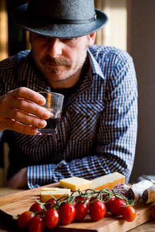 Man drinking wine and eating mediterranean food in cafe - CUF52389