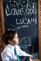 Boy in school uniform beside blackboard at home - CUF52392