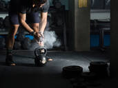 Man powdering hands before lifting kettlebell in gym - CUF52398