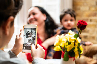 Boy taking smartphone photo mother and toddler brother celebrating mothers day, over shoulder view - CUF52404