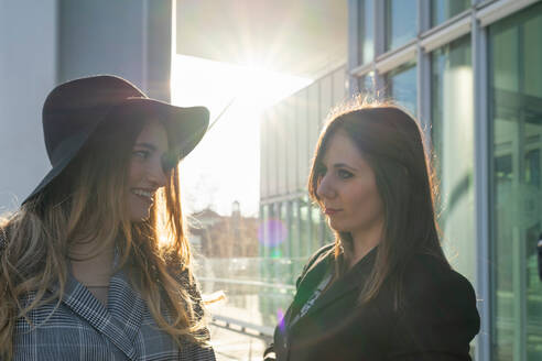 Young women chatting outside sunlit office building, Turin, Piemonte, Italy - CUF52407