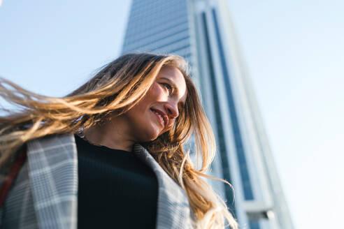 Young woman with long blond hair in front of skyscraper, low angle view, Turin, Piemonte, Italy - CUF52419