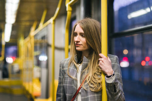 Young woman with long blond hair standing in train carriage at dusk - CUF52431