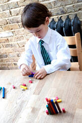Boy in school uniform playing with colour sticks at home - CUF52440