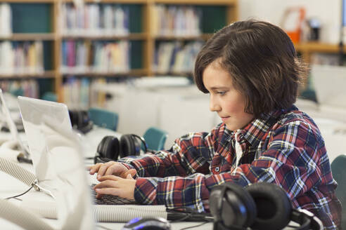 Caucasian boy using laptop in library - BLEF08057
