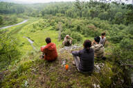 Caucasian friends admiring scenic view from rural hilltop - BLEF08128