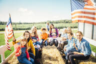 Caucasian family waving American flags on hay ride - BLEF08197