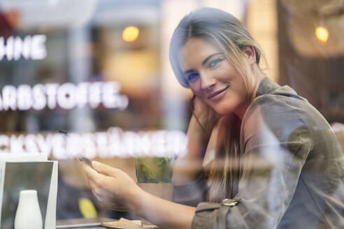 Young businesswoman in a cafe, seen through window - DIGF07110