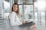 Young businesswoman using tablet in a waiting area - DIGF07134