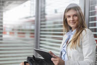 Young businesswoman using tablet in a waiting area - DIGF07137