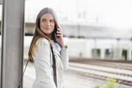 Young businesswoman using smartphone, standing on station - DIGF07143