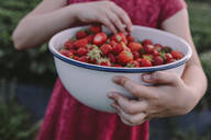 Midsection of girl holding strawberries in bowl at back yard - OGF00003
