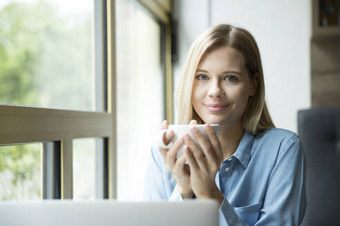 Businesswoman with cup of coffee, in front of laptop - MFRF01331