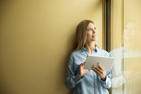 Businesswoman with tablet looking out of window - MFRF01334