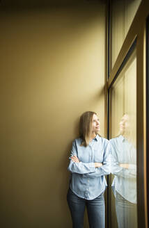 Businesswoman looking out of window - MFRF01340