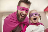 Father and daughter playing superhero and superwoman - ZEDF02489