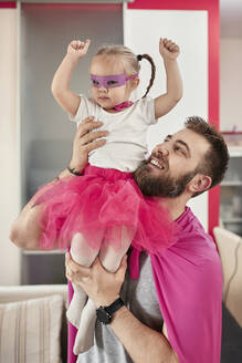 Father and daughter playing superhero and superwoman - ZEDF02504