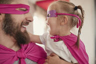 Father and daughter playing super hero and superwoman - ZEDF02510
