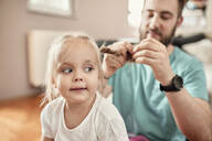 Father braiding hair of his daughter - ZEDF02513