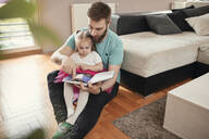 Father and daughter reading a book - ZEDF02516
