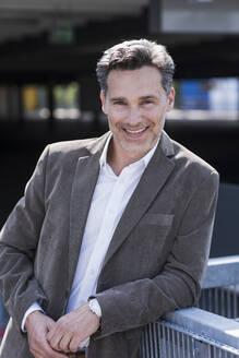 Portrait of businessman, wearing grey suit jacket - UUF18156