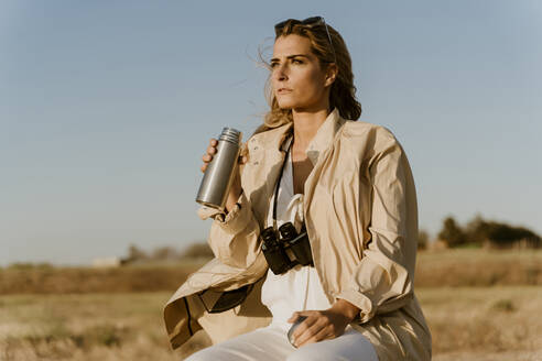 Female traveller with binoculars drinking thermos flask - ERRF01600